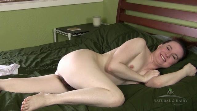 Брюнетка показывает волосатую писю на кровати